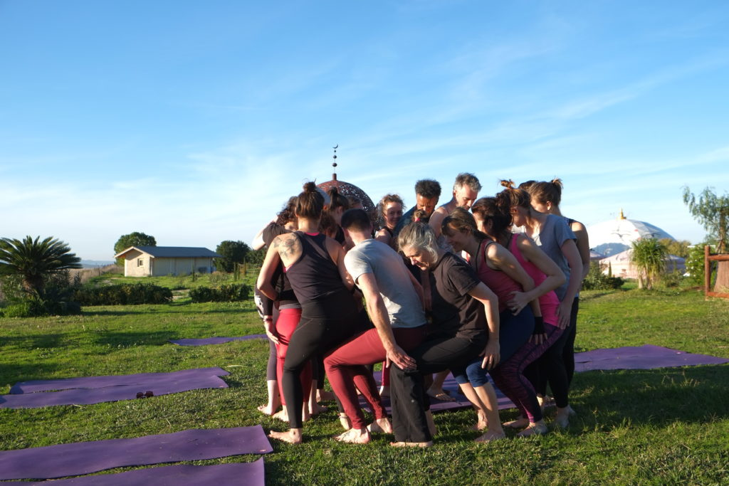 Stand in a circle and sit down on each other's laps. Acro-yoga!