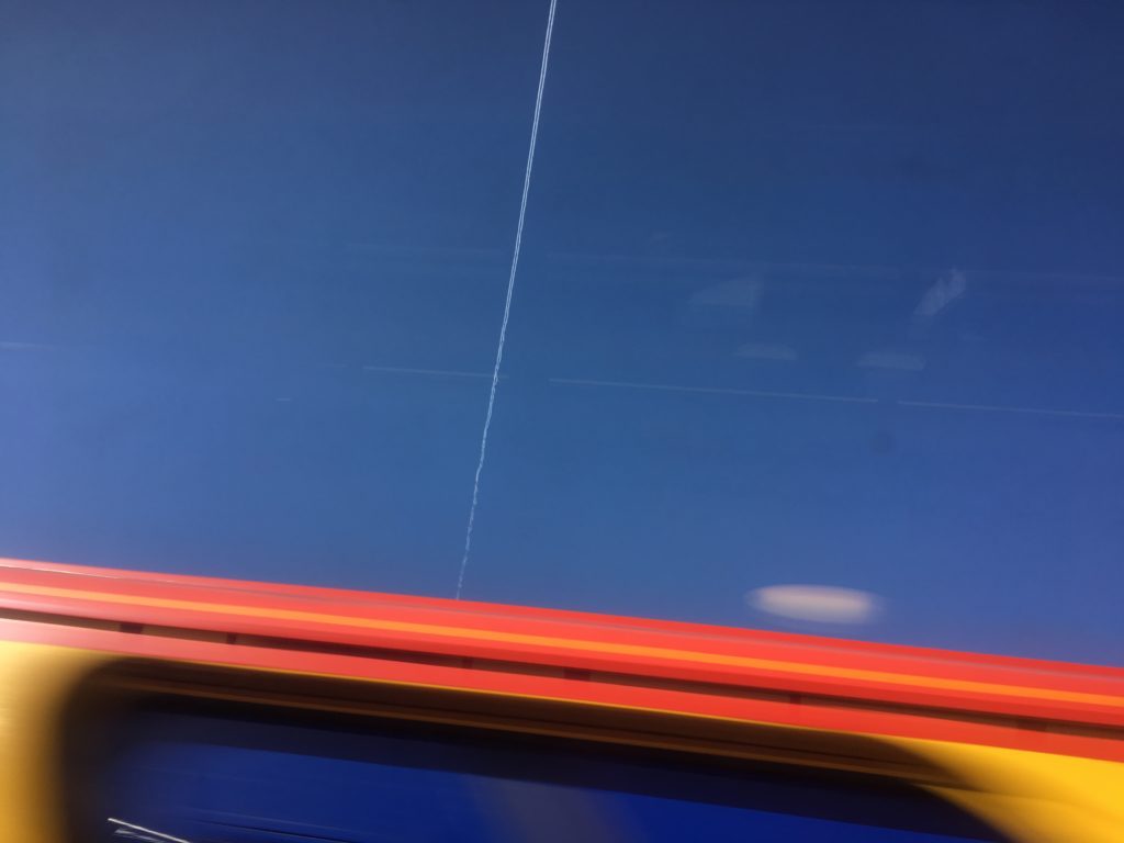 Central contrail cuts the blue sky over the roof of a passing train