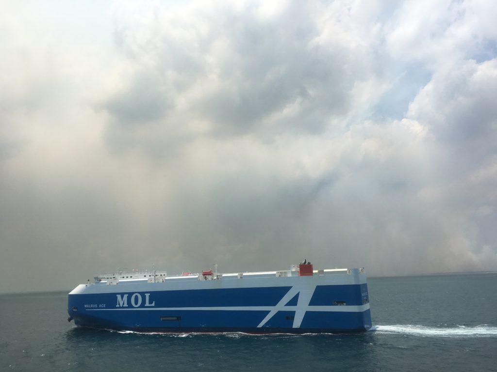 Car carrier against backdrop of Moreton Island fire